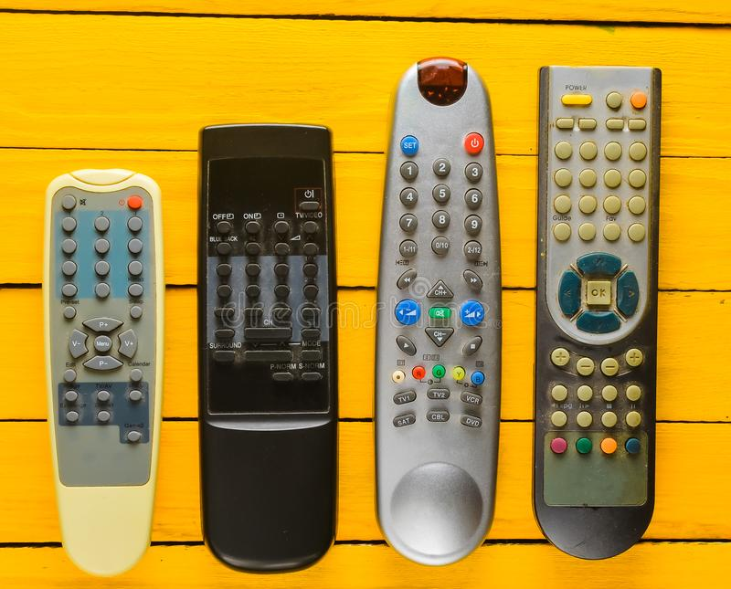 Many obsolete TV remotes on a yellow rustic wooden table. Top view. stock image