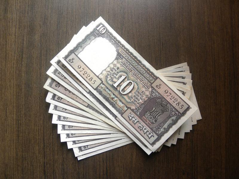 Many old ten rupees note. Many black color old 10 rupees India banknote kept on wooden table royalty free stock images