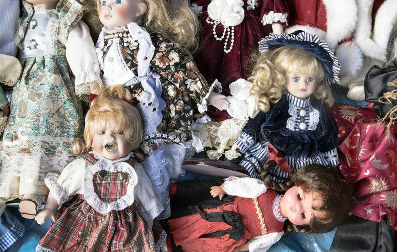 Many old toy dolls for sale on the flea market royalty free stock photo