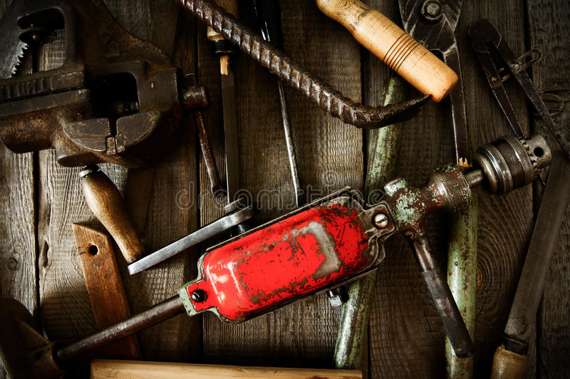 Many old working tools ( mount, drill, corner and. The old working tool. Many old working tools ( mount, drill, corner and others) on a wooden background royalty free stock photography