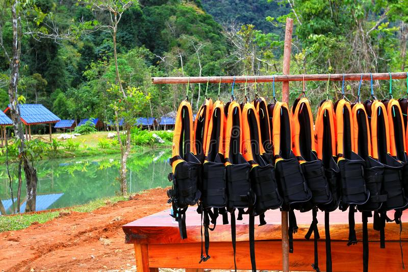 Many orange life jacket or vest hanging on clothes line or washing line for rent. And tourist wearing before swimming in lake at Blue Lagoon 3, VangVieng, Laos royalty free stock photo