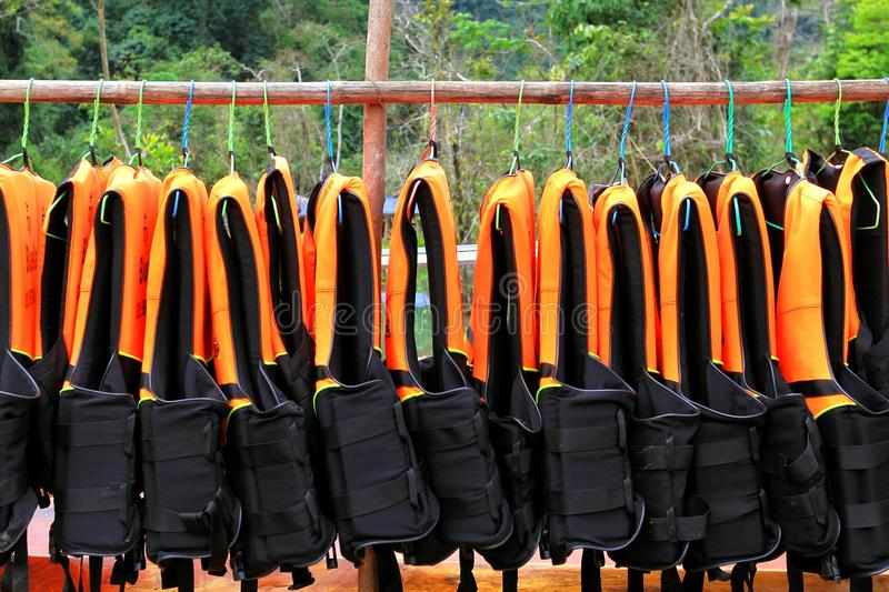 Many orange life jacket or life vest hanging on clothes line royalty free stock photography