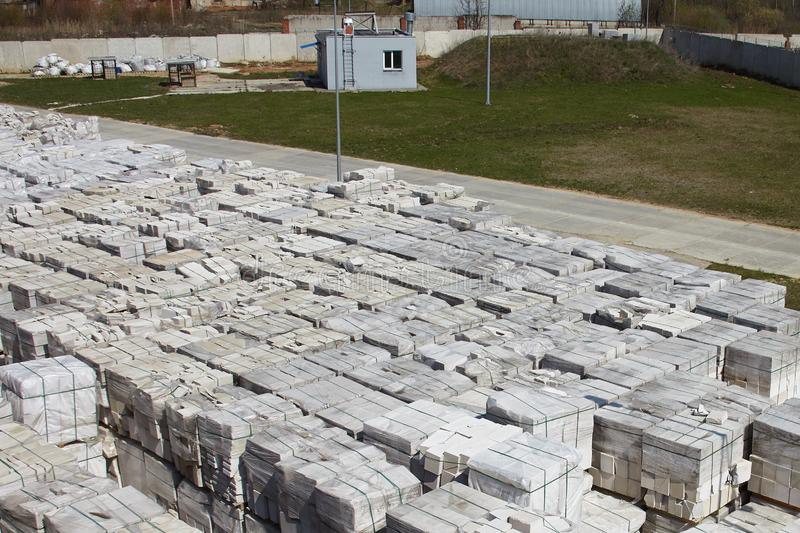 Many packages of autoclaved aerated concrete on pallets put one on the other on an outdoor factory warehouse. Top view of. Industrial area stock photography
