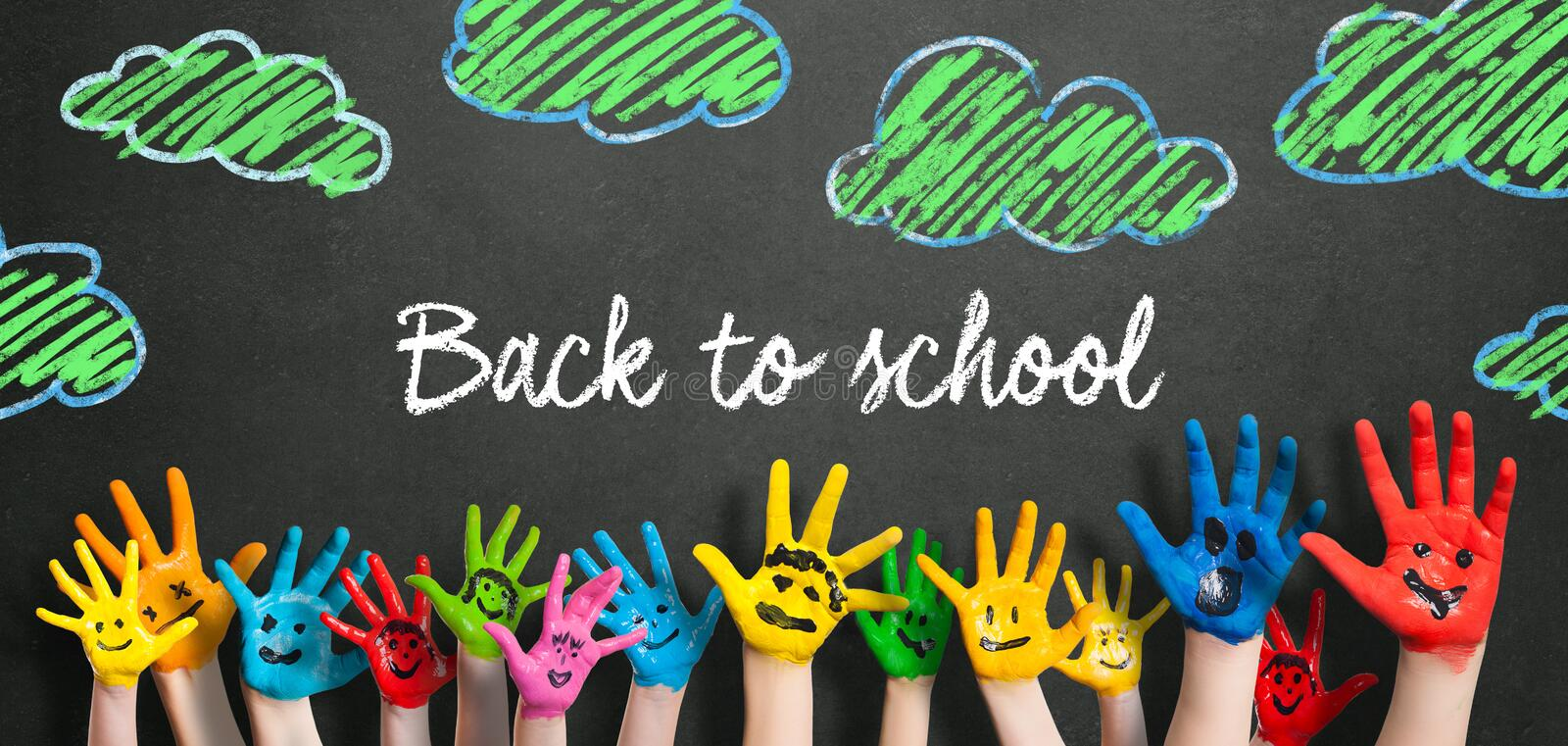 Many painted kids hands with smileys and the message `Back to school` royalty free stock photography
