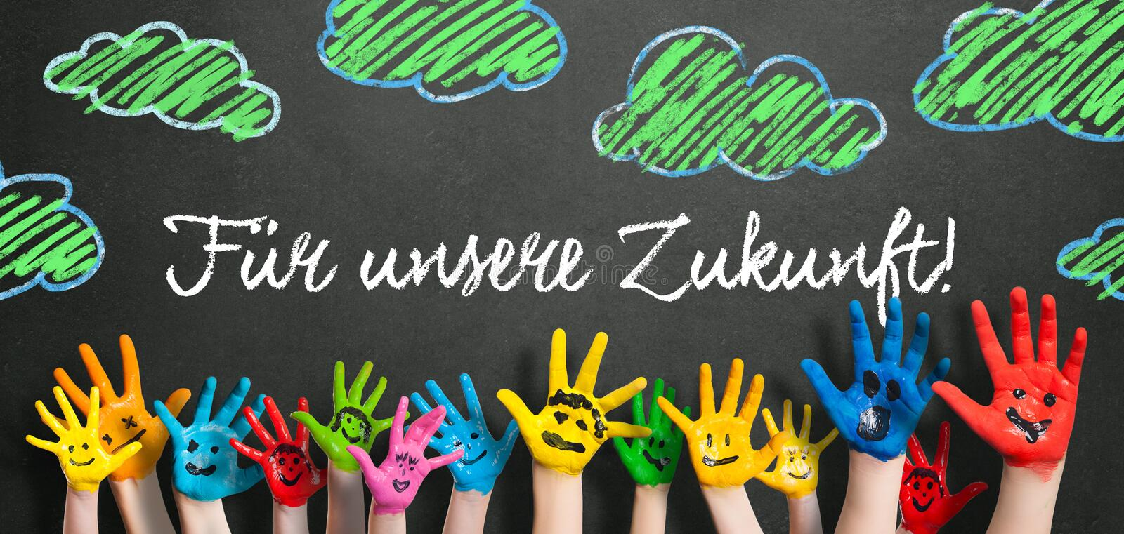 Many painted kids hands with smileys and the message `For our feature!` in German. On a blackboard stock photography