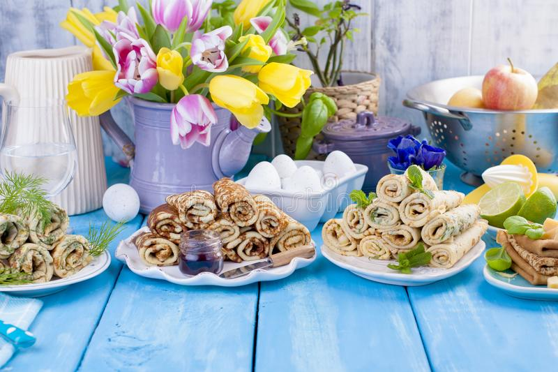 Many pancakes with different fillings and flavors. Delicious traditional Russian food in the spring. Homemade baking. Flowers and stock photo
