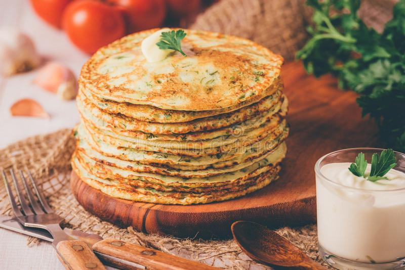 Many pancakes with fresh herbs and sour cream sauce on a wooden table. Traditional Ukrainian or Russian pancakes. Maslenitsa. Traditional dishes on the holiday stock photos
