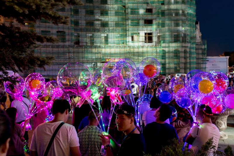 LED balloons people, holding many lighted balloons filled with toys and lights royalty free stock images