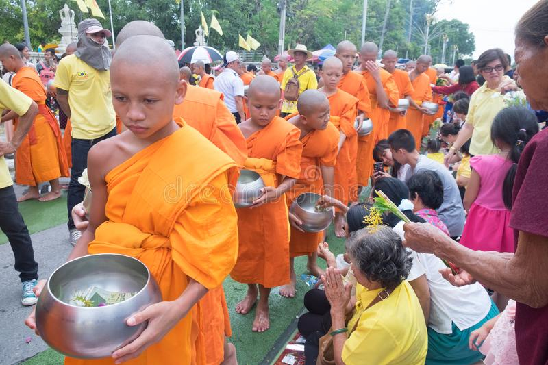 Many people give flowers to Buddhist monks for alms stock image