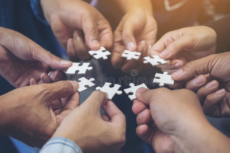 Many people hands holding a jigsaw puzzle in circle together. Closeup image of many people hands holding a jigsaw puzzle in circle together royalty free stock photo