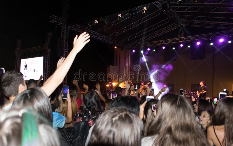 Many people have fun during an outdoor concert. People with their hands in the air applaud and dance to the music of a pop artist. Night concert. Bucuresti royalty free stock photo