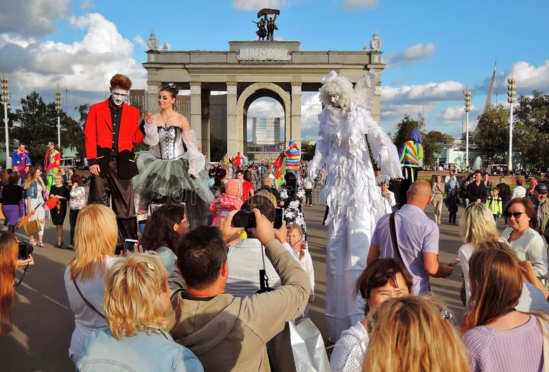 Many people take pictures of street actors in Moscow. MOSCOW - AUGUST 01, 2015: Street actors pose for photos in VDNH park in Moscow. They walk on stilts. Many royalty free stock photo