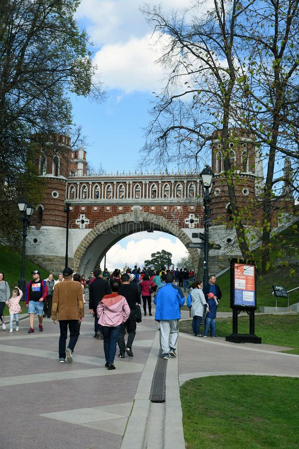 Many people walk under Figured Bridge. Architecture of Tsaritsyno park in Moscow. Color photo. Many people walk under Figured Bridge. Architecture of Tsaritsyno royalty free stock photo