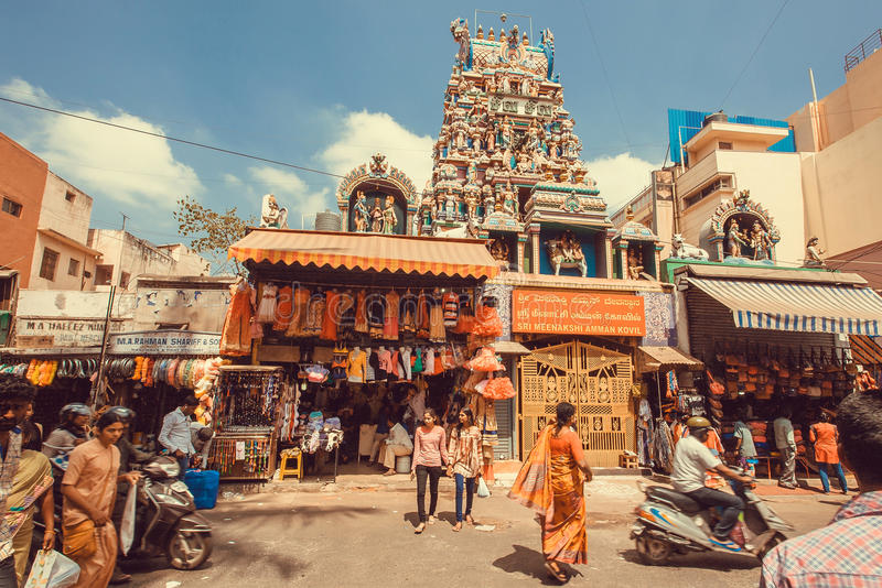 Many people walking on street with market and Hindu temple stock photo
