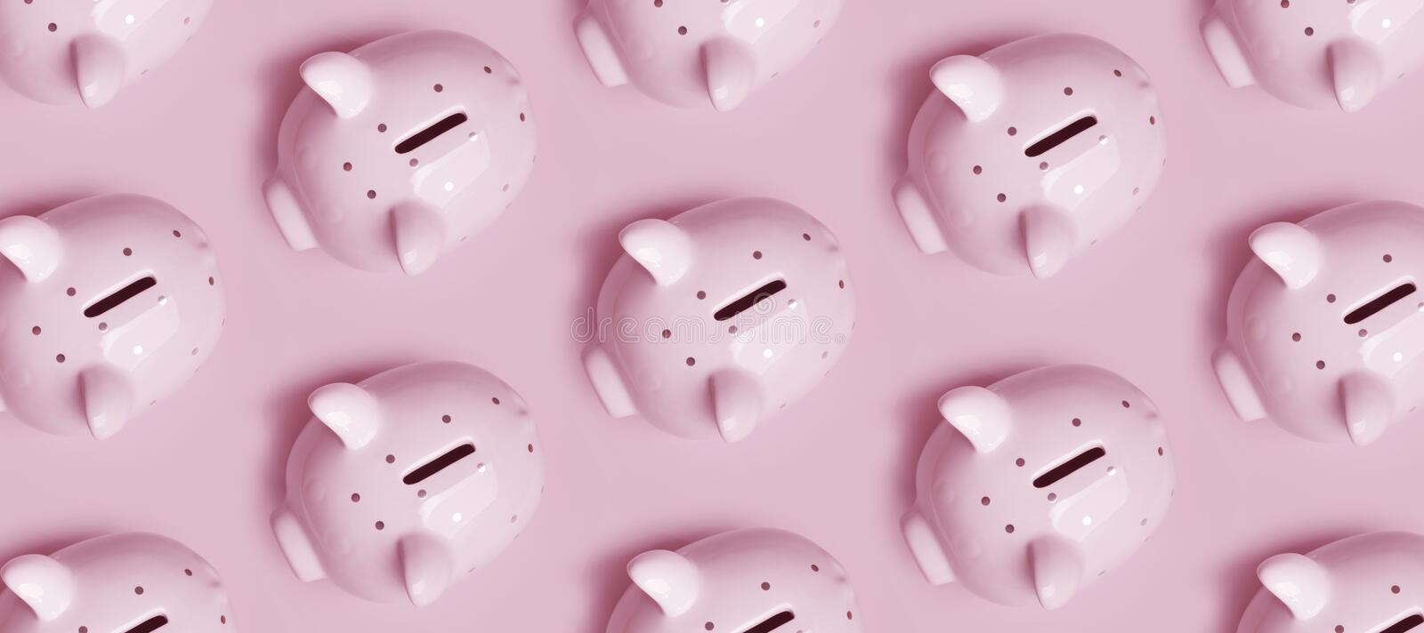 Many piggy banks in rows on pink background, top view royalty free stock photography