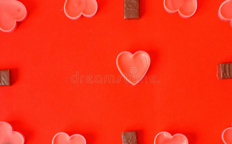 Many Pink Candle hearts and chocolate candies on red background. Happy valentines day.Many Pink Candle hearts and chocolate candies on red background.. Romantic royalty free stock photos