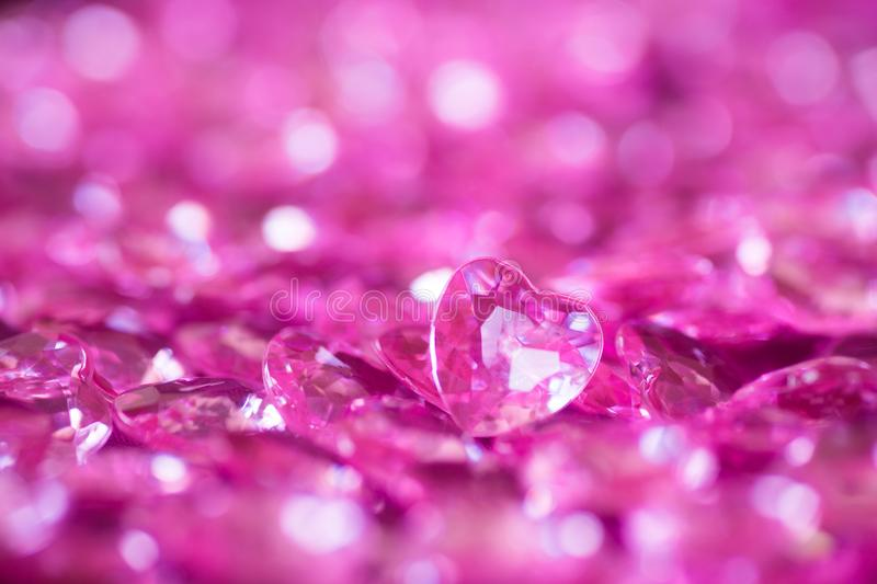 Many pink little crystal hearts with bokeh background. royalty free stock images