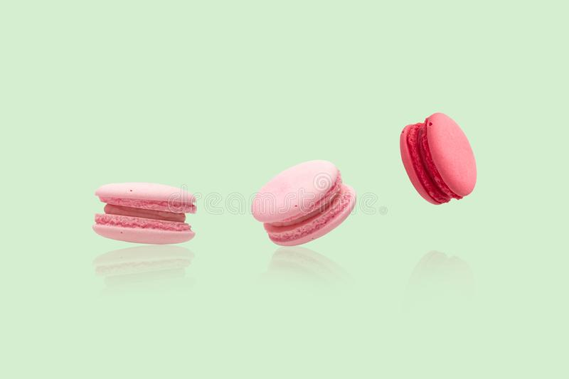 Many pink macaroons on the green background royalty free stock photos