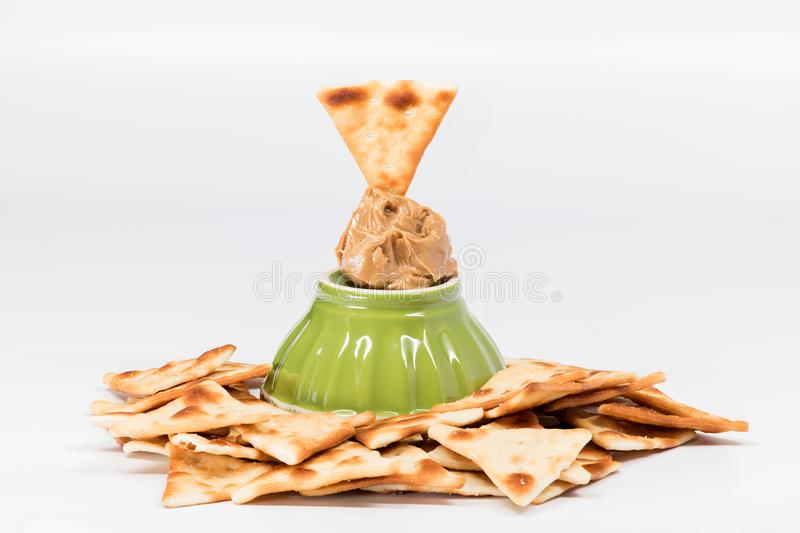 Many pita crackers and a dap of peanut butter with green bowl stock images