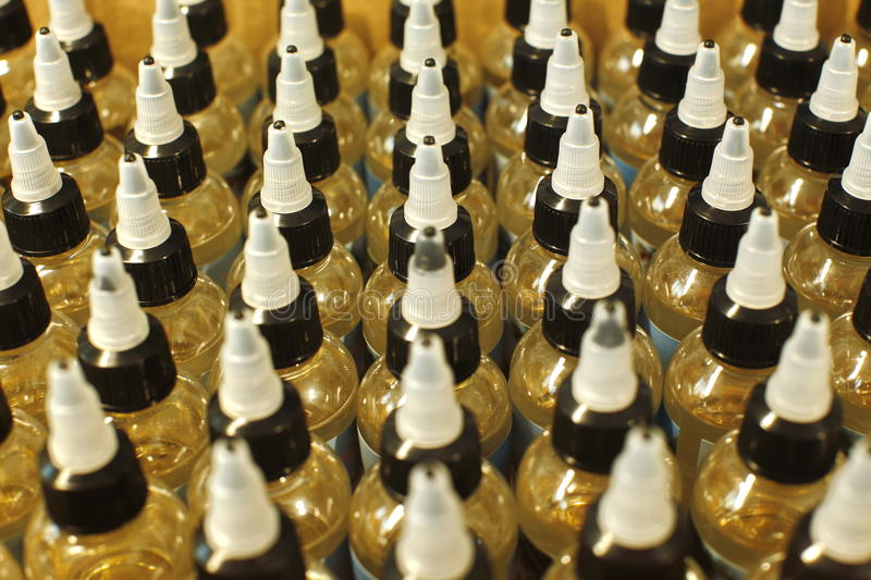 Many plastic bottles with caps with liquid for electronic cigarettes top view close up royalty free stock images