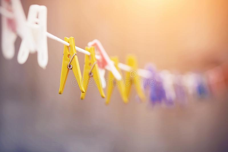 Many plastic clothespins hang on a white clothesline royalty free stock photography