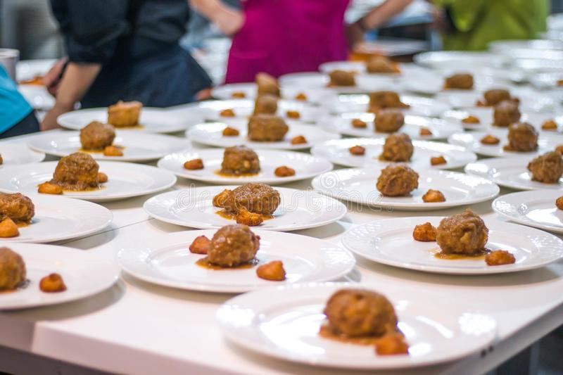 Many plates dish of meetballs being prepared in commercial industrial professional kitchen galley for event party royalty free stock image