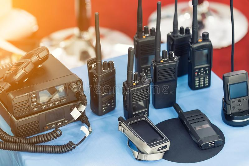 Many portable radio transceivers on table at technology exhibition. Different walkie-talkie radio set. Communication devices. Choice for military and civil use stock images