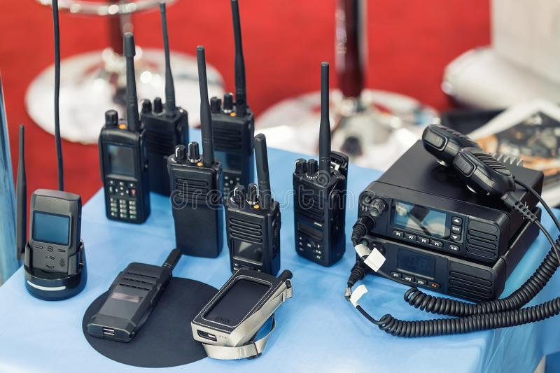 Many portable radio transceivers on table at technology exhibition. Different walkie-talkie radio set. Communication devices. Choice for military and civil use stock photo