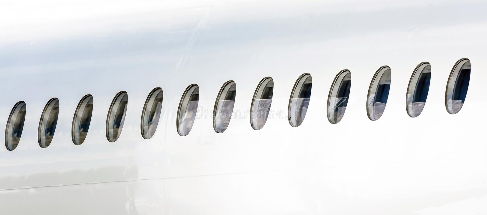 Many portholes in a row on the fuselage of a white airplane. Many portholes in a row on the fuselage of a white airplane stock image