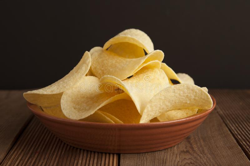 Many potato chips in round plate isolated on rustic wooden table and black background. Snack food. stock images