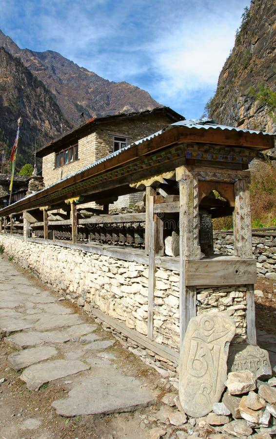 Many prayer wheels in nepal village stock photography