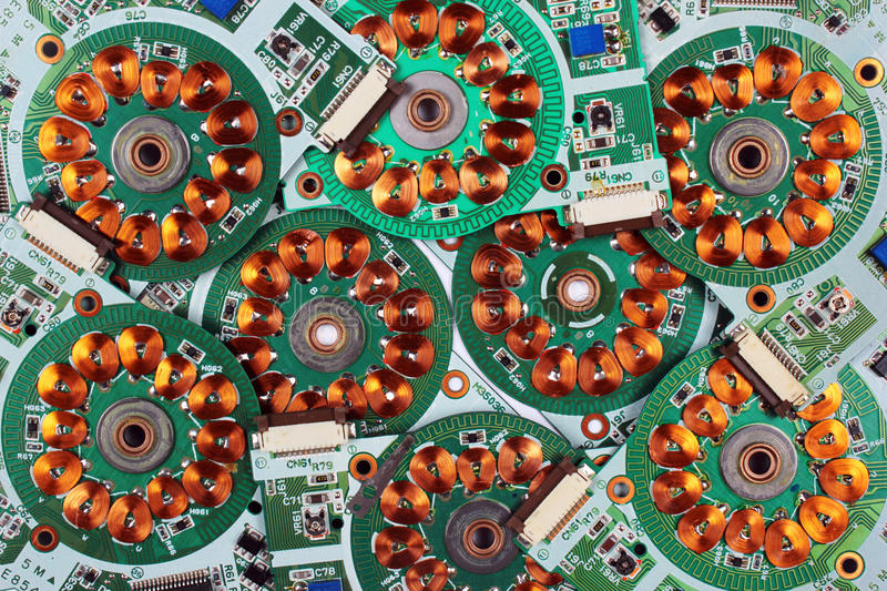Many printed circuit boards from old floppy drives with windings and coils. Of brushless motors. Abstract electronics background royalty free stock images