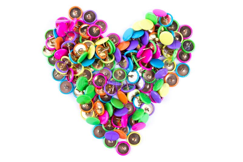 Many push pins in form of heart. Heap of colorful push pins on white background. Variety of push pins of different colors stock photos