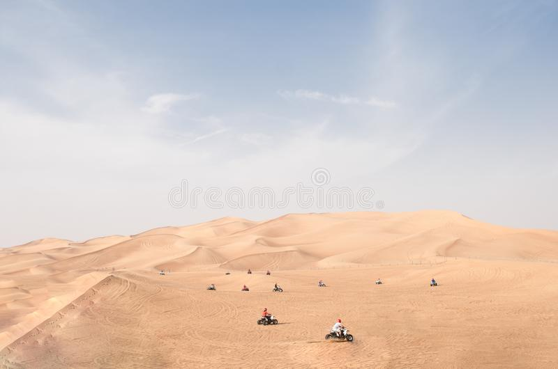 Many Quad bike ATV riders riding at station on red desert hills royalty free stock photography