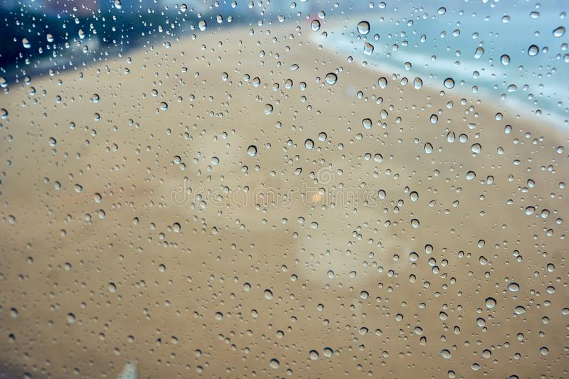 Many rain drops on the window with a blurred view of the beach royalty free stock photo