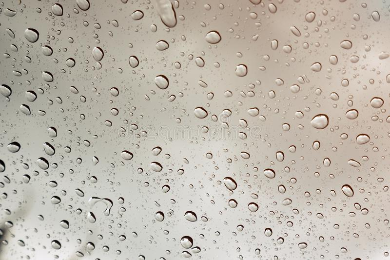 Many raindrop on clear glass during rainy season. As background stock photography
