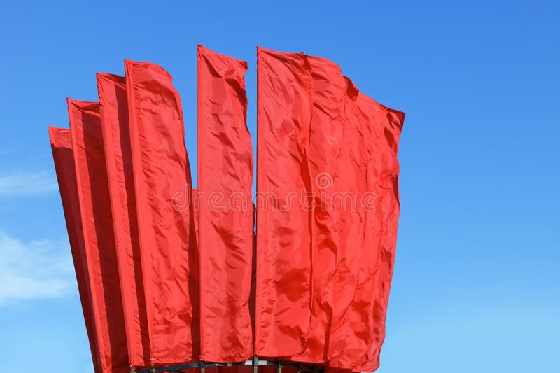 Many red flags waving in the wind against the blue sky. royalty free stock photos