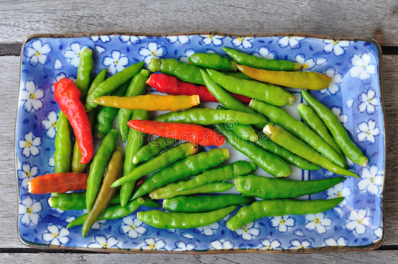 Many red and green Thai Chillis in plate on wooden table. stock photos