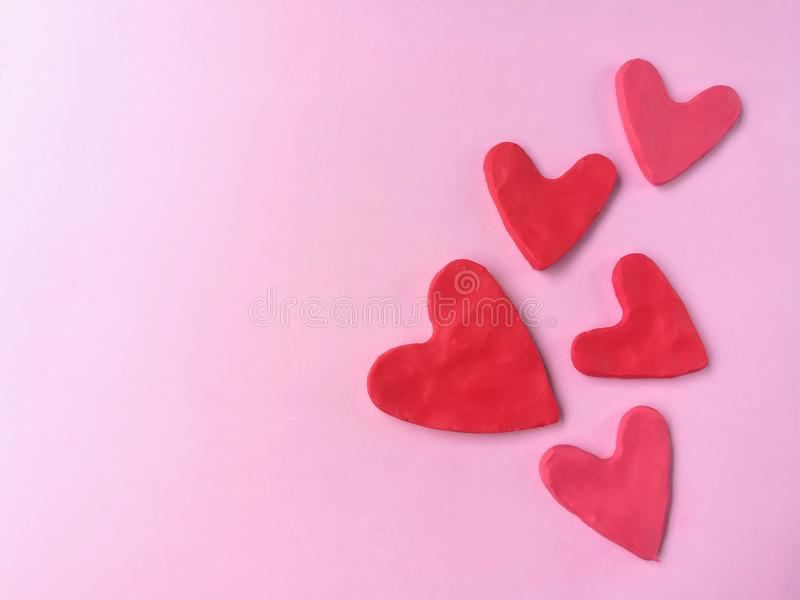 Many red heart, plasticine clay, pink background, cute shaped dough royalty free stock photography