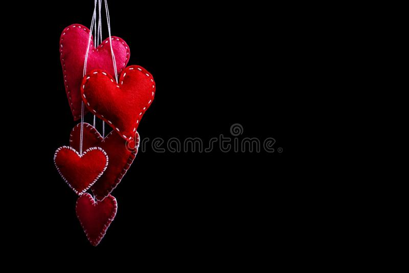 Many red hearts of felt on a rope. Handmade isolate on black background stock photo