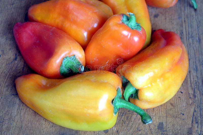 Many red and orange whole sweet peppers on wooden surface royalty free stock photo