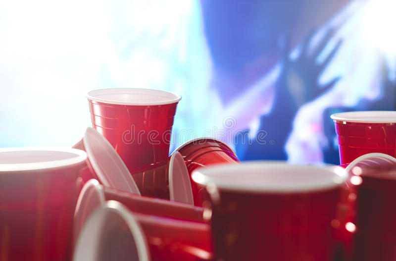 Many red party cups with blurred celebrating people in the background. College alcohol containers in mixed positions. stock photo