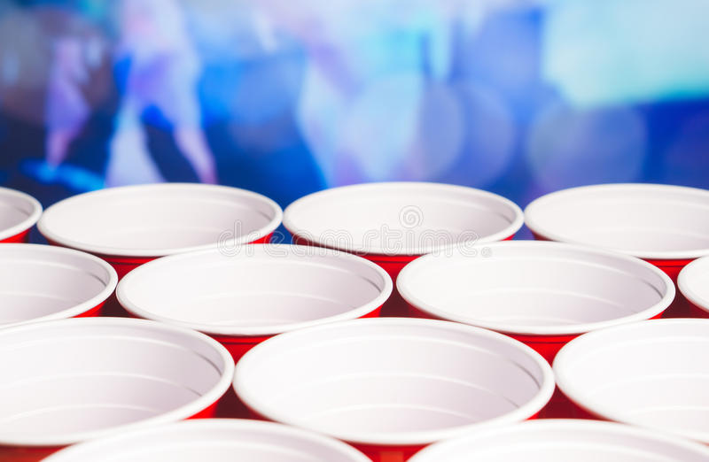Many red party cups with blurred celebrating people in the background. Low angle close up of college alcohol containers. royalty free stock photos