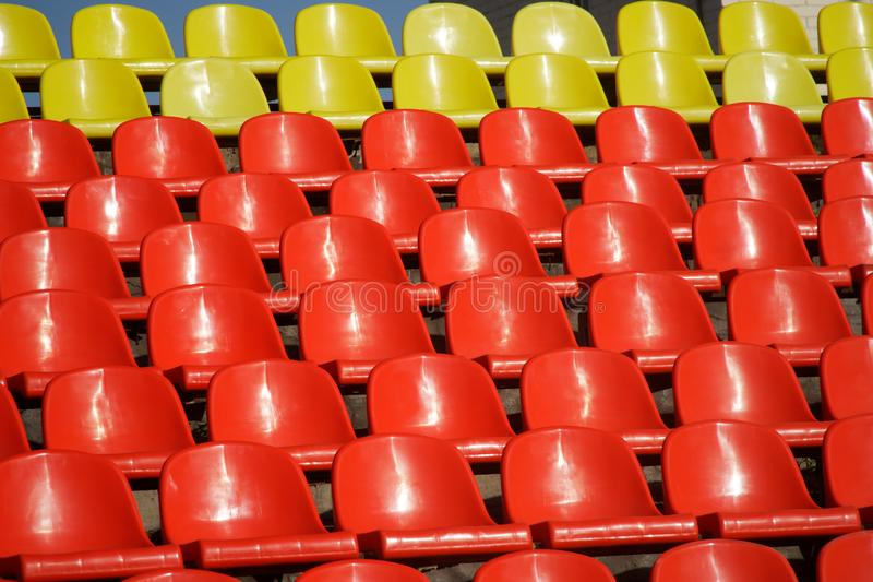 Many red and yellow plastic seats in an open stadium. Free access. Empty seats, without spectators. Waiting for the spectacle. Daylight royalty free stock photography
