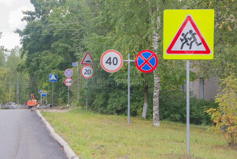 Many road signs along the road. Traffic signs. Traffic signs along the road stock images