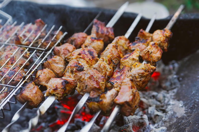 Many roast meat pieces on skewer. shish kebab cooking process royalty free stock photos