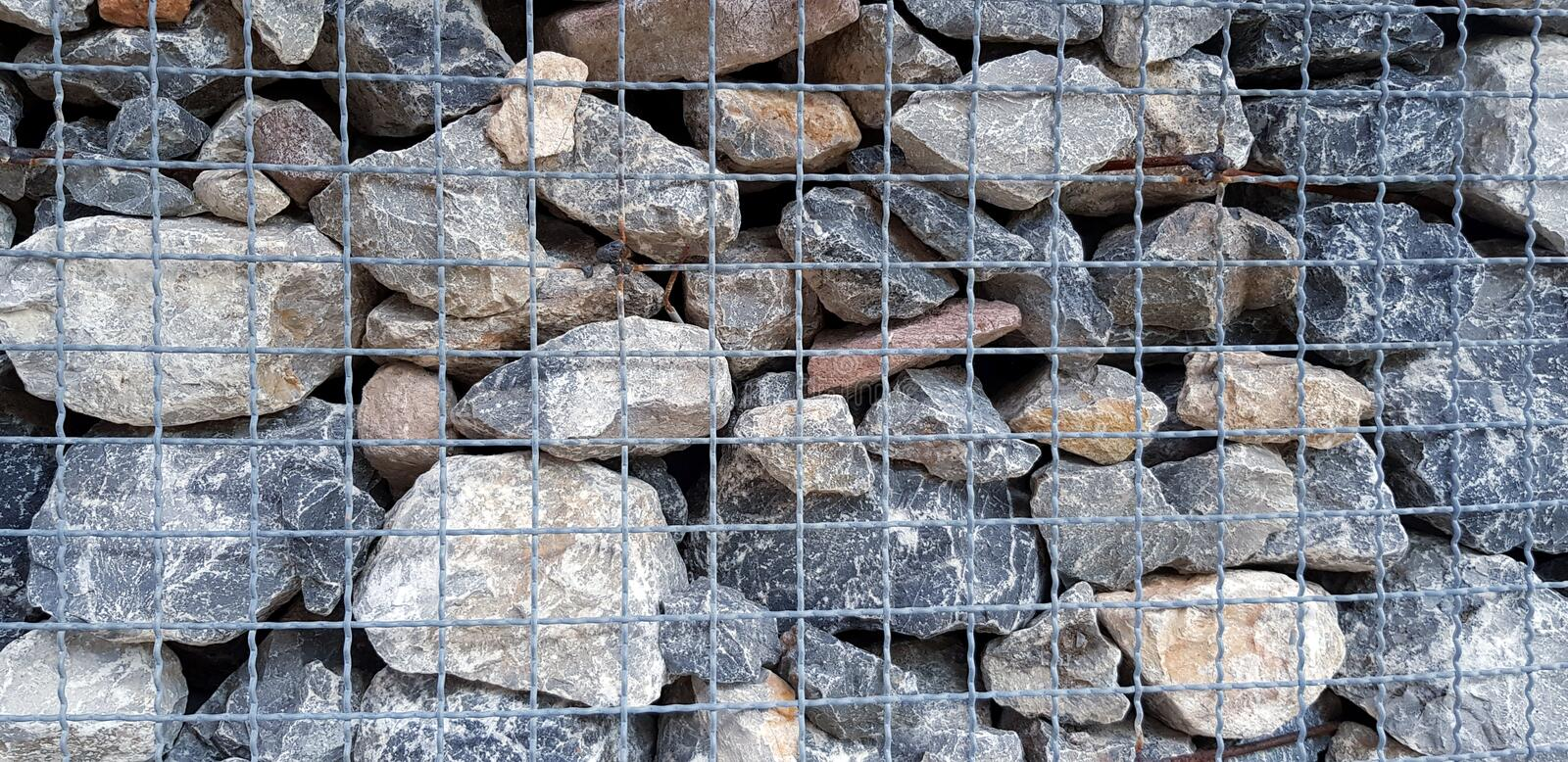 Many rock, stone or limestone in steel netting or net barrier for background stock images