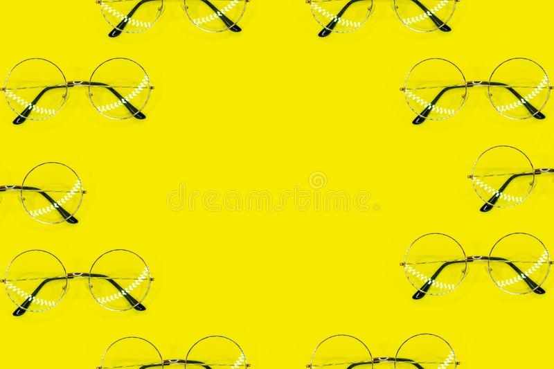 Many round glasses lying as frame on yellow background. Top view point, flat lay royalty free stock image