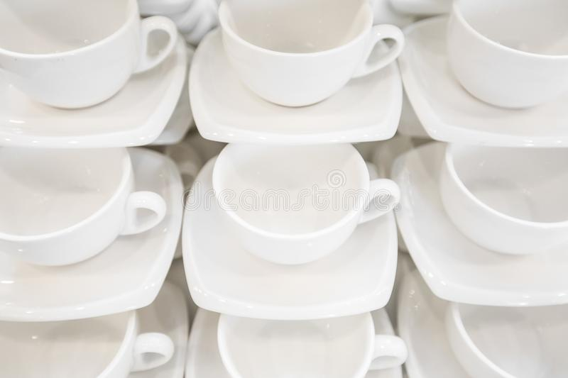 Many rows clean white coffee cup, tea spoon and saucer on table. Empty mug set in row prepare for coffee break stock image