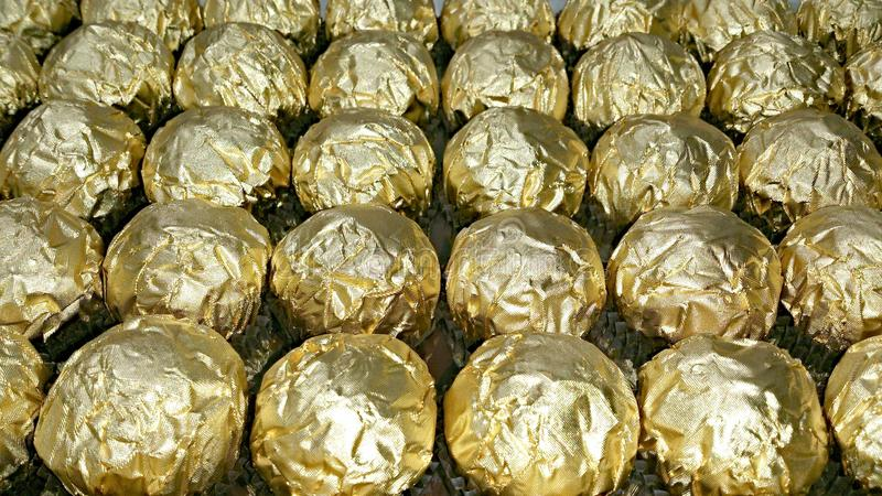 Many rows of golden wrappers stock photo
